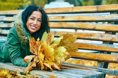 Smiling young attractive woman with autumn maple leaves in park at fall outdoors Royalty Free Stock Photography
