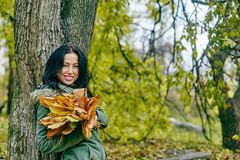 Smiling young attractive woman with autumn maple leaves in park at fall outdoors Royalty Free Stock Photos