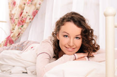 Smiling young attractive woman lying on bed Royalty Free Stock Image
