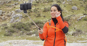 Smiling young backpacker using a selfie stick Royalty Free Stock Photo