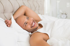 Smiling young bald man resting in bed Royalty Free Stock Images