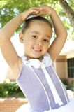 Smiling young ballet dancer. Wearing tutu dress with hands over head posing outdoors Stock Photo