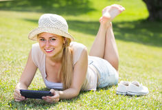 Smiling young barefoot woman holding mobile phone in hands Stock Images