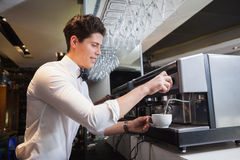 Smiling young barista making cup of coffee Royalty Free Stock Images