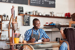 Smiling young barista talking to a customer in his cafe. Smiling young African barista talking to a customer and writing down an order in a notebook while Royalty Free Stock Images