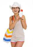 Happy beach woman in hat holding sun screen creme Stock Image