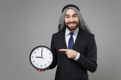 Smiling young bearded arabian muslim businessman in keffiyeh kafiya ring igal agal classic suit isolated on gray