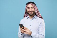 Smiling young bearded arabian muslim man in keffiyeh kafiya ring igal agal casual clothes  on pastel blue