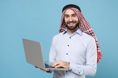 Smiling young bearded arabian muslim man in keffiyeh kafiya ring igal agal casual clothes posing  on pastel blue