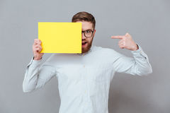Smiling young bearded businessman holding copyspace blank. Image of smiling young bearded businessman holding copyspace blank and pointing standing over grey Royalty Free Stock Photography