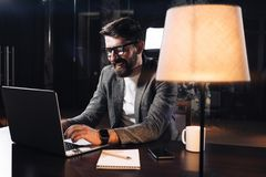 Smiling young bearded businessman working on contemporary notebook in loft office at night. Project manager wearing glasses typing text on laptop royalty free stock photo