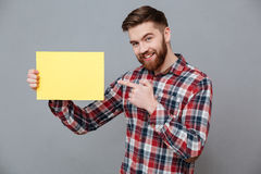 Smiling young bearded man holding copyspace blank. Image of smiling young bearded man holding copyspace blank and pointing standing over grey background Royalty Free Stock Photo