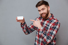 Smiling young bearded man holding copyspace business card. Image of smiling young bearded man holding copyspace business card and pointing standing over grey Stock Images