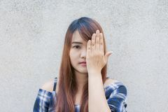 Smiling young beautiful asian woman closing her eyes with hands on concrete wall background. Vintage effect style pictures stock images