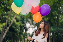 Smiling young beautiful asian women with long brown hair in the park. With rainbow-colored air balloons in her hands. Smiling young beautiful asian woman with stock image