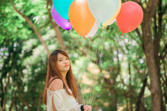 Smiling young beautiful asian women with long brown hair in the park. With rainbow-colored air balloons in her hands. Smiling young beautiful asian woman with stock photo