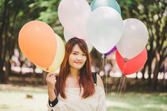 Smiling young beautiful asian women with long brown hair in the park. With rainbow-colored air balloons in her hands. Smiling young beautiful asian woman with royalty free stock image
