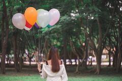 Smiling young beautiful asian women with long brown hair in the park. With rainbow-colored air balloons in her hands. Smiling young beautiful asian woman with royalty free stock photography