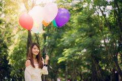 Smiling young beautiful asian women with long brown hair in the park. With rainbow-colored air balloons in her hands. Smiling young beautiful asian woman with royalty free stock photo
