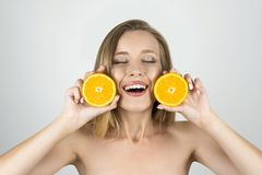 Smiling young beautiful blond woman holding oranges in her hands looking pleased isolated white background royalty free stock photo