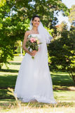 Smiling young beautiful bride with bouquet in park Royalty Free Stock Images