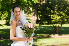 Smiling young beautiful bride with bouquet in park Stock Images