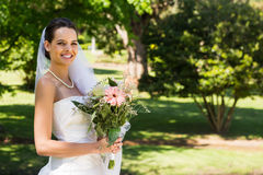 Smiling young beautiful bride with bouquet in park Royalty Free Stock Photos
