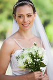 Smiling young beautiful bride with bouquet in park Stock Image