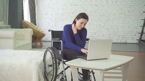 Portrait of a smiling young beautiful disabled woman in a wheelchair, working at home on a laptop, remote work royalty free stock image