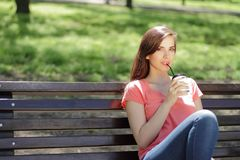 Smiling young beautiful girl in green park with different emotio. Ns, drinking coffee on bench Royalty Free Stock Photography