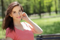 Smiling young beautiful girl in green park with different emotio. Ns, positive looking in camera Royalty Free Stock Image