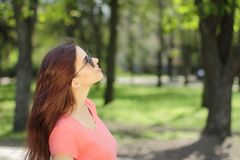 Smiling young beautiful girl in green park with different emotio. Ns, positive looking up Stock Photos
