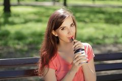 Smiling young beautiful girl in green park with different emotio. Ns, positive looking in camera drinking coffee Royalty Free Stock Photos