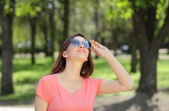 Smiling young beautiful girl in green park with different emotio. Ns, positive looking up Royalty Free Stock Photo