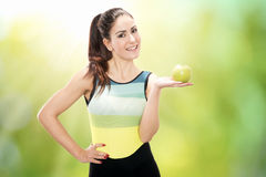 Smiling young beautiful woman with an apple stock images