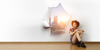 Smiling young beautiful woman sitting on the floor. Mixed media royalty free stock photo