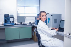 Smiling young biochemist using laptop at her desk Stock Image