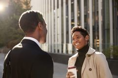 Smiling young black businesswoman standing on the street with a takeaway coffee, talking to her male colleague, selective focus stock image