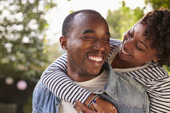 Smiling young black couple piggyback in garden, eyes closed Stock Photo