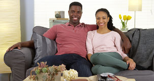 Smiling young black couple sitting on sofa looking at camera Royalty Free Stock Photos