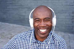 Smiling young black guy listening to music with headphones Royalty Free Stock Photography