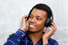 Smiling young black man with headphones listening to music Royalty Free Stock Photos