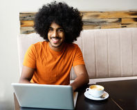 Smiling young black man with laptop on cafe table royalty free stock photo