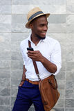 Smiling young black man with mobile phone and bag. Portrait of a smiling young black man with mobile phone and bag standing against gray background Royalty Free Stock Photo
