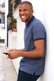 Smiling young black man with mobile phone standing outside. Portrait of smiling young black man with mobile phone standing outside Stock Photos