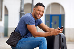 Smiling young black man sitting outside with suitcase and mobile phone. Portrait of smiling young black man sitting outside with suitcase and mobile phone Stock Images
