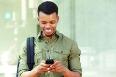 Smiling young black man with smart phone and backpack Royalty Free Stock Image