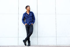 Smiling young black man standing against wall Royalty Free Stock Image