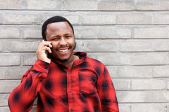 Smiling young black man talking on mobile phone Royalty Free Stock Images