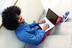 Smiling young black man using laptop outside Stock Photo